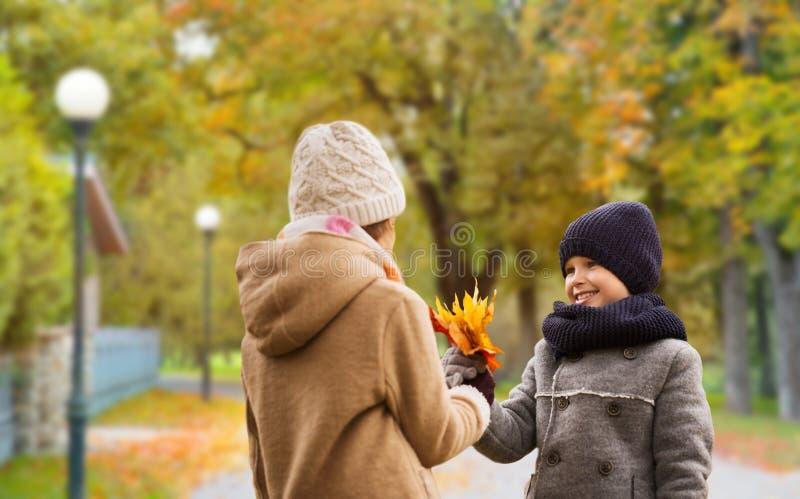 De glimlachende kinderen in de herfst parkeren stock afbeeldingen