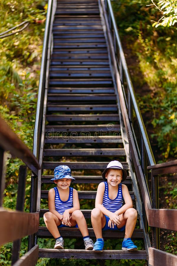 De glimlachende kinderen in de zomer Panama en de borrels zitten op de stappen in de zomer Verticale foto stock afbeelding