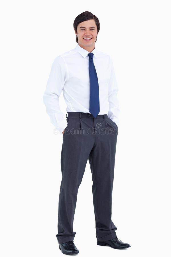 De glimlachende kleinhandelaar met van hem dient zijn zakken in royalty-vrije stock afbeelding