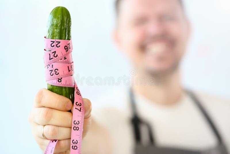 De glimlachende Komkommer van Chef-kokmeasuring coiled green royalty-vrije stock fotografie