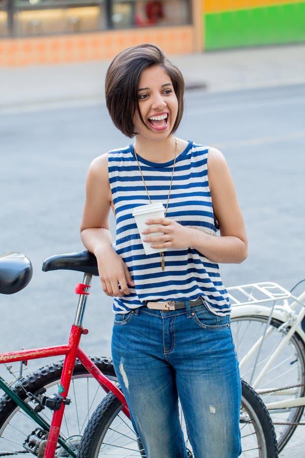 De glimlachende lachende jonge vrouw van het hipster Latijnse Columbiaanse meisje met kort haarloodje in blauwe gescheurde jeans stock foto's