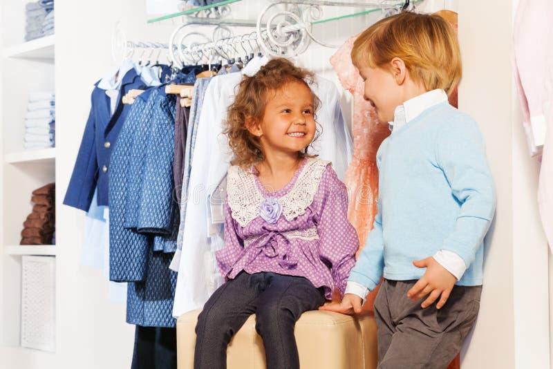 De glimlachende leuke jongen bekijkt meisje terwijl het winkelen stock afbeeldingen