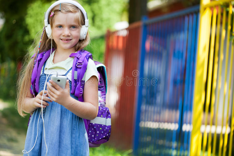 De glimlachende leuke meisjes met rugzak luisteren aan muziek royalty-vrije stock foto's