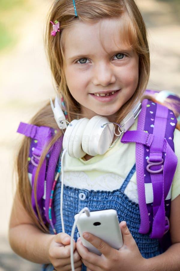 De glimlachende leuke meisjes met rugzak luisteren aan muziek stock fotografie