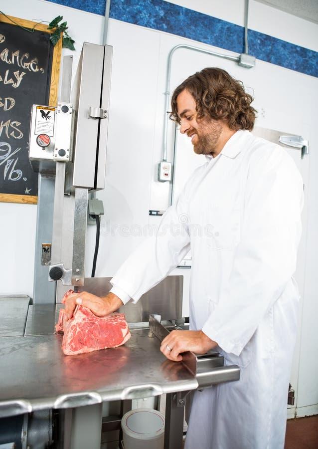 De glimlachende Machine van Slagersslicing meat in stock afbeelding
