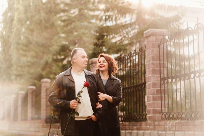 De glimlachende man en de vrouw van vijftig jaar gaan hand in hand op een stadsstraat in de zomer stock fotografie