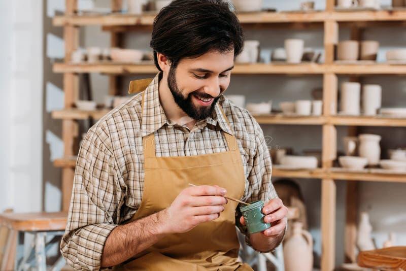 de glimlachende mannelijke verf en de borstel van de pottenbakkersholding stock afbeelding