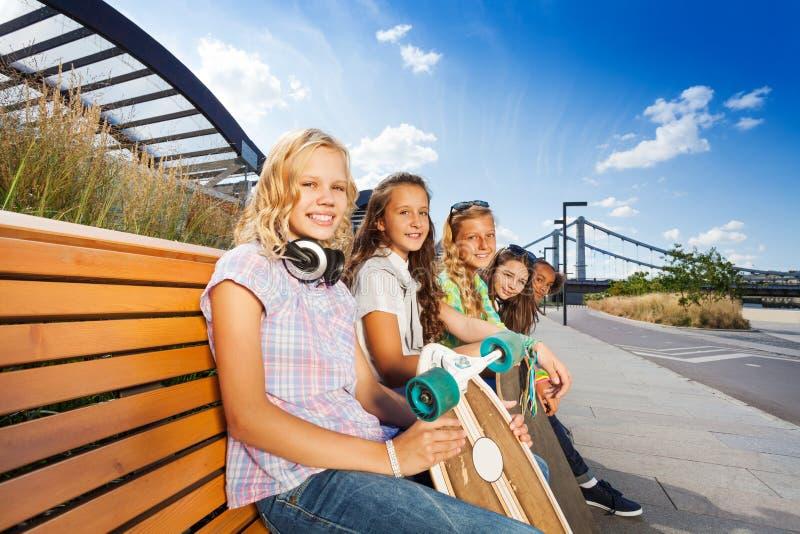 De glimlachende meisjes zitten op houten bank met skateboard royalty-vrije stock foto's