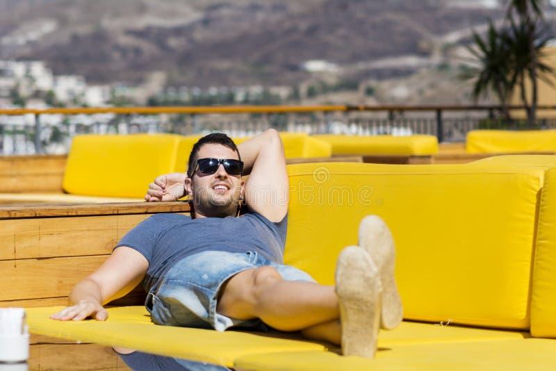 De glimlachende mens die van de de zomervakantie genieten die op a liggen sunbed in een overzeese bar stock afbeelding