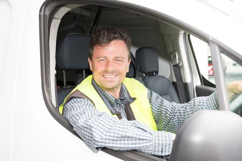 De glimlachende mens die van de leveringsbestuurder zijn bestelwagen drijven royalty-vrije stock foto