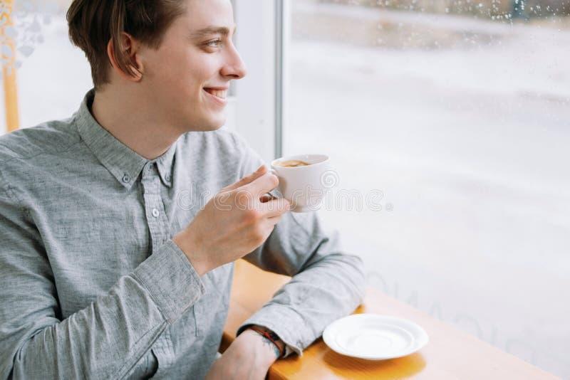 De glimlachende mens geniet van de ontspannen vrije tijd van de kopkoffie koffie royalty-vrije stock foto's