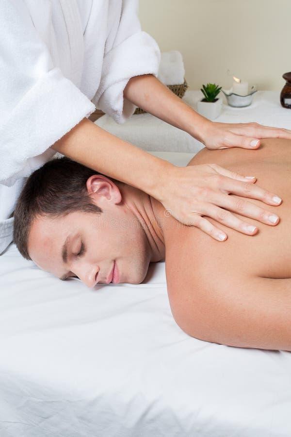 De glimlachende mens krijgt een massage royalty-vrije stock afbeelding