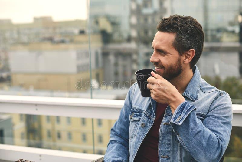 De glimlachende mens met baard houdt kop op hand stock fotografie