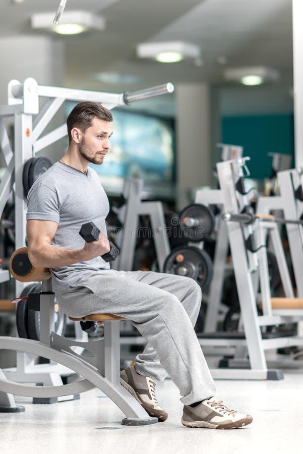 De glimlachende mens van de atletenbodybuilder bij exerci van biceps-brachiispieren stock afbeelding