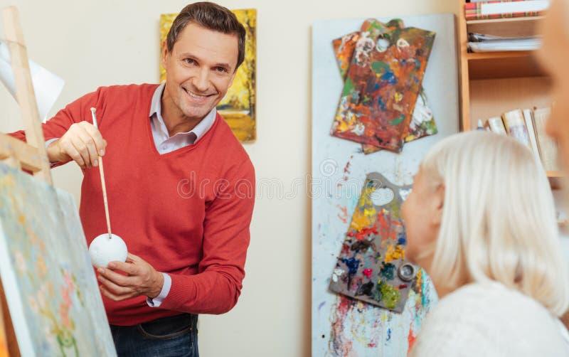 De glimlachende mensen van het mensenonderwijs in het schilderen van studio royalty-vrije stock afbeelding