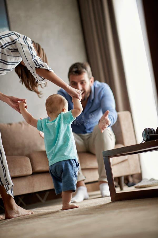De glimlachende moeder en de vader leren thuis om hun kindjongen te lopen stock foto