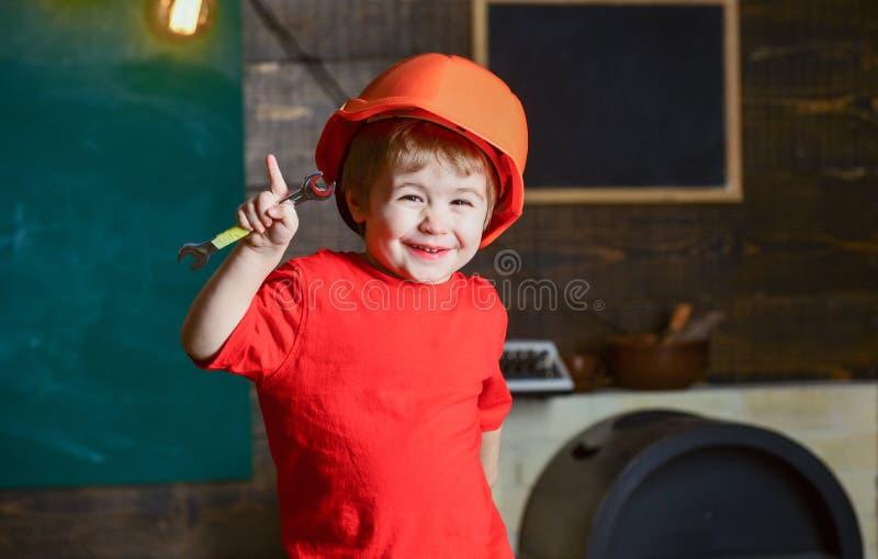 De glimlachende moersleutel van de jong geitjeholding en het benadrukken met zijn vinger Leuke jongen die pret in workshop hebben stock afbeelding