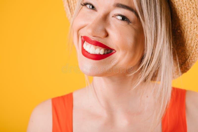 De glimlachende mooie aanbiddelijke vrouw van het tandenblonde De warme rood en gele kleuren van de de zomertijd stock afbeelding