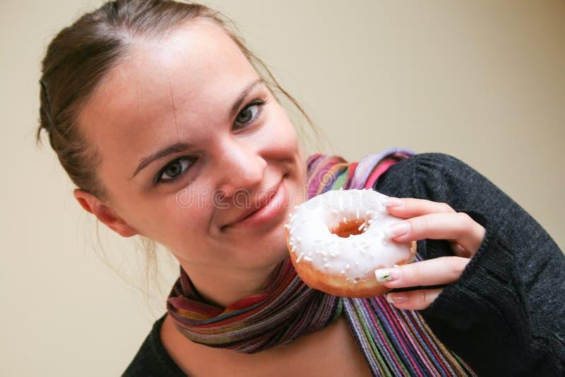 De glimlachende mooie vrouw houdt een doughnut in witte glans stock afbeelding