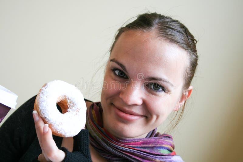 De glimlachende mooie vrouw houdt een doughnut in witte glans stock fotografie