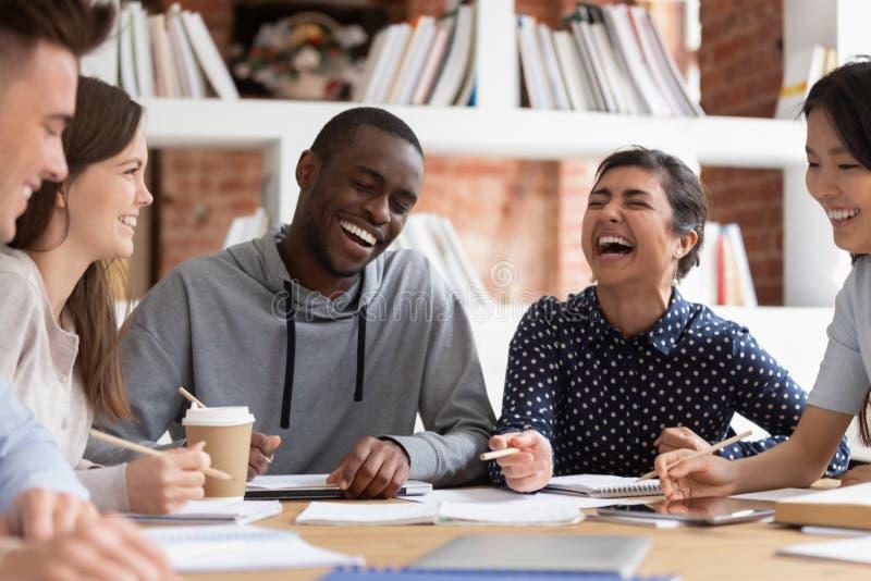 De glimlachende multiraciale jongeren hebt pret samen bestuderend stock fotografie