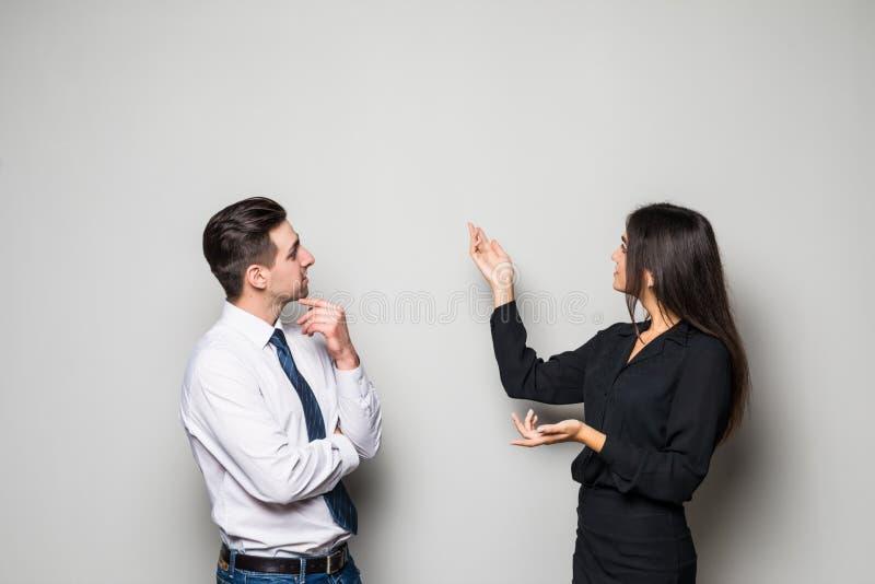 De glimlachende onderneemster en de zakenman converseren tegen grijze achtergrond royalty-vrije stock afbeeldingen
