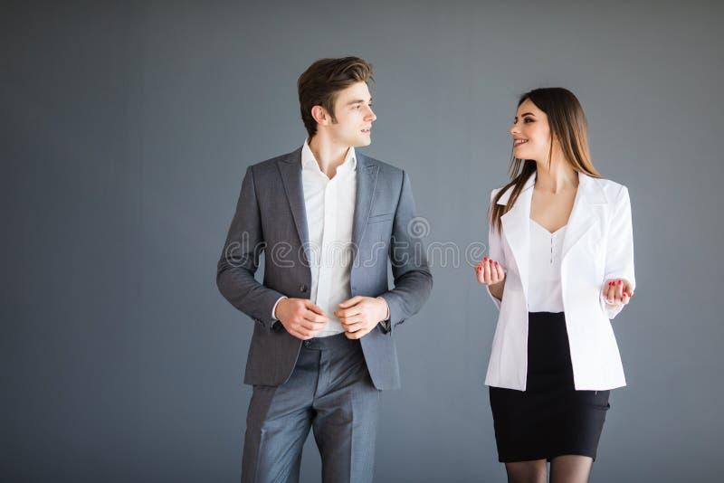 De glimlachende onderneemster en de zakenman converseren tegen grijze achtergrond Bedrijfs concept royalty-vrije stock foto