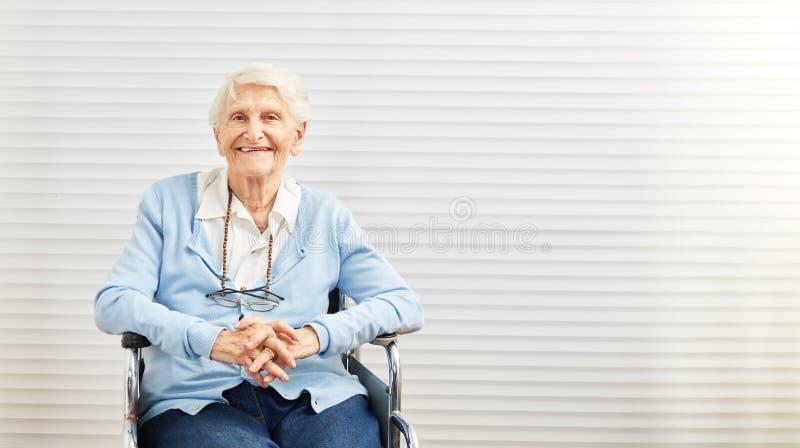 De glimlachende oude vrouw zit in rolstoel in pensioneringshuis royalty-vrije stock fotografie