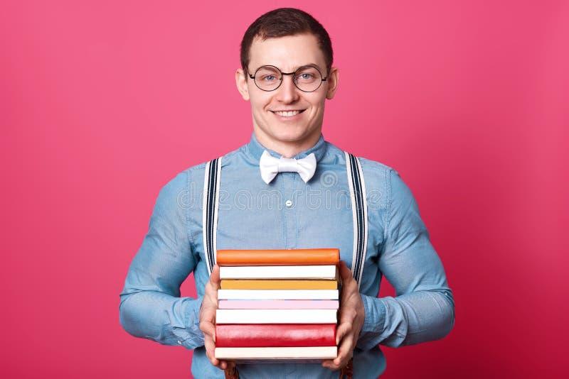 De glimlachende positieve mens houdt bos van kleurrijke boeken in beide handen, stellen geïsoleerd over roze achtergrond in studi royalty-vrije stock afbeelding