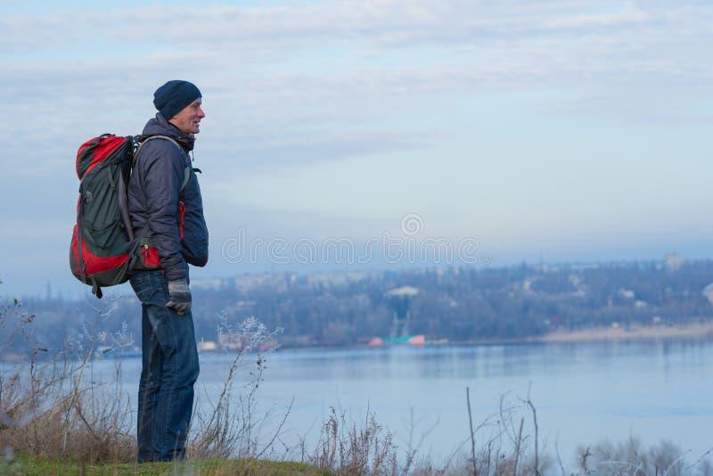 De glimlachende reiziger met een rugzak bevindt zich op een heuvel door ri royalty-vrije stock afbeelding