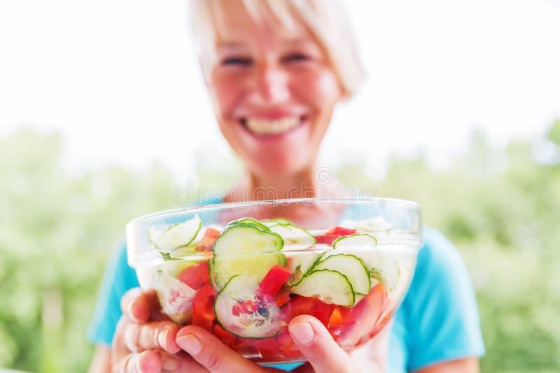 De glimlachende rijpe vrouw houdt een kom met salade stock afbeeldingen