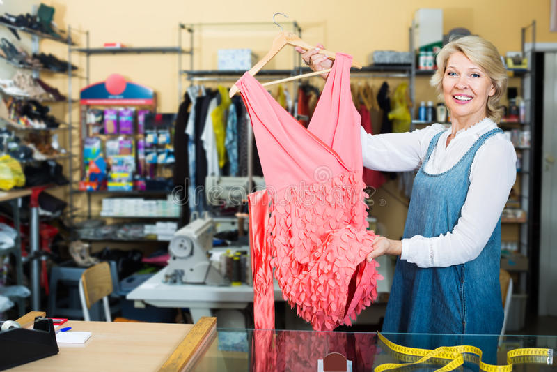 De glimlachende rijpe vrouwelijke kleermaker die kleding hebben dient binnen het naaien in at royalty-vrije stock foto's
