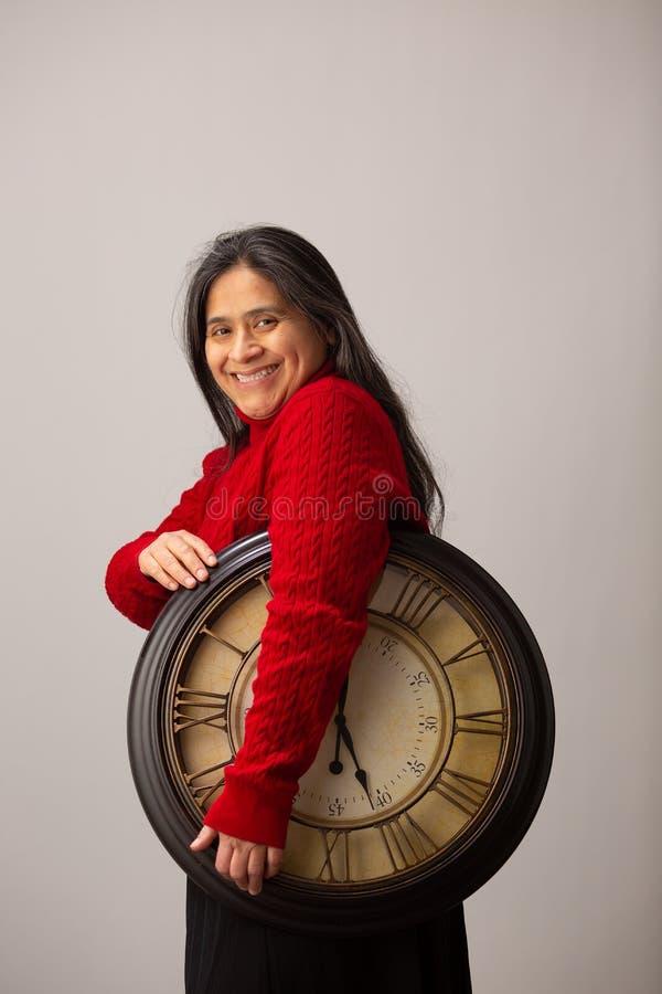 De glimlachende Spaanse Vrouw houdt Klok en glimlacht aan Camera stock afbeeldingen