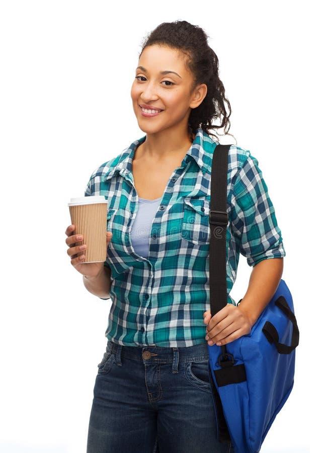 De glimlachende student met zak en haalt koffiekop weg stock afbeelding