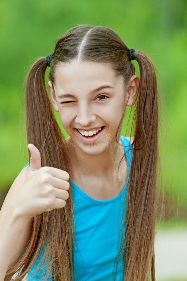 De glimlachende tiener neemt omhoog grote duimen op stock afbeeldingen