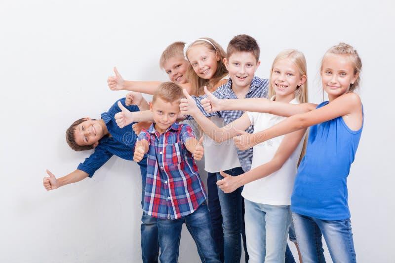 De glimlachende tieners die o.k. teken op wit tonen stock fotografie