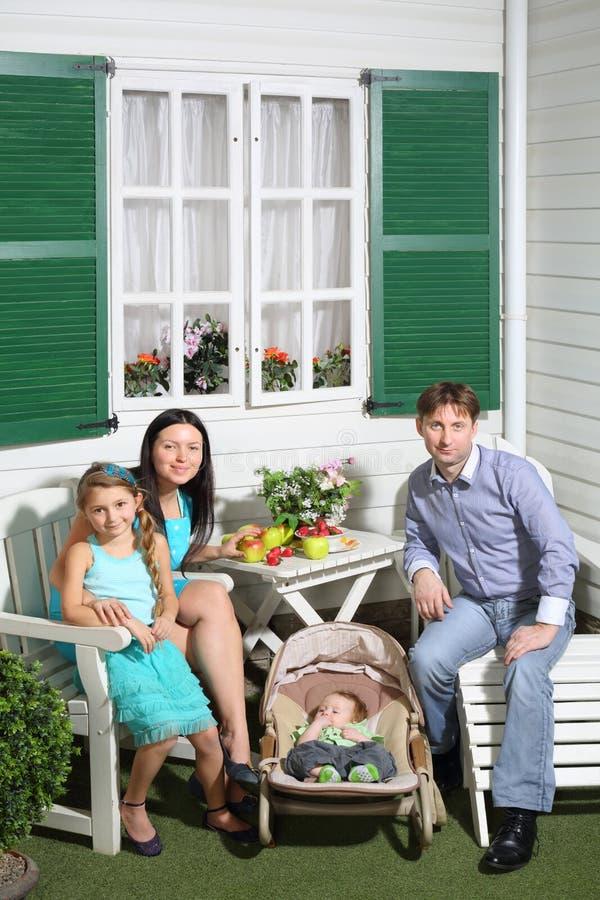 De glimlachende vader, de moeder, de baby en weinig dochter zitten bij lijst stock fotografie