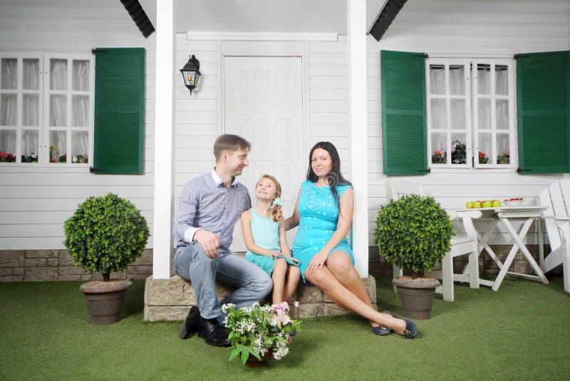 De glimlachende vader, de moeder en de dochter zitten op portiek royalty-vrije stock afbeelding