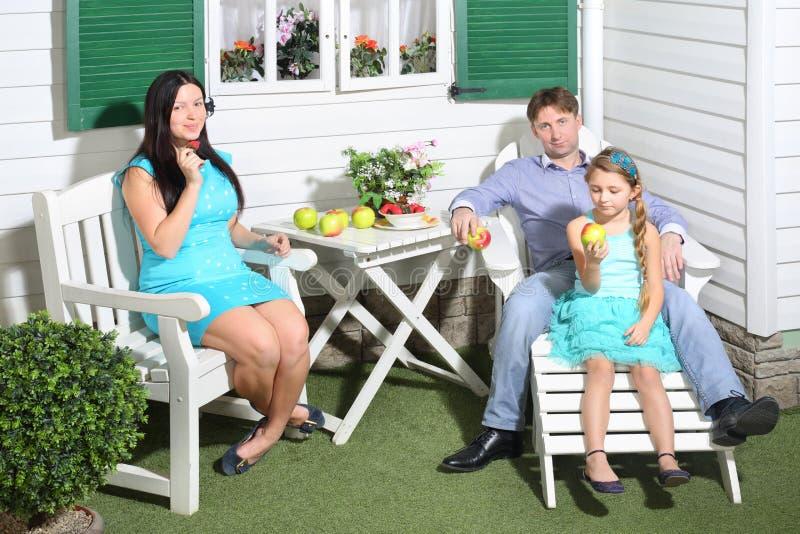 De glimlachende vader, de moeder en weinig dochter zitten bij lijst stock afbeeldingen