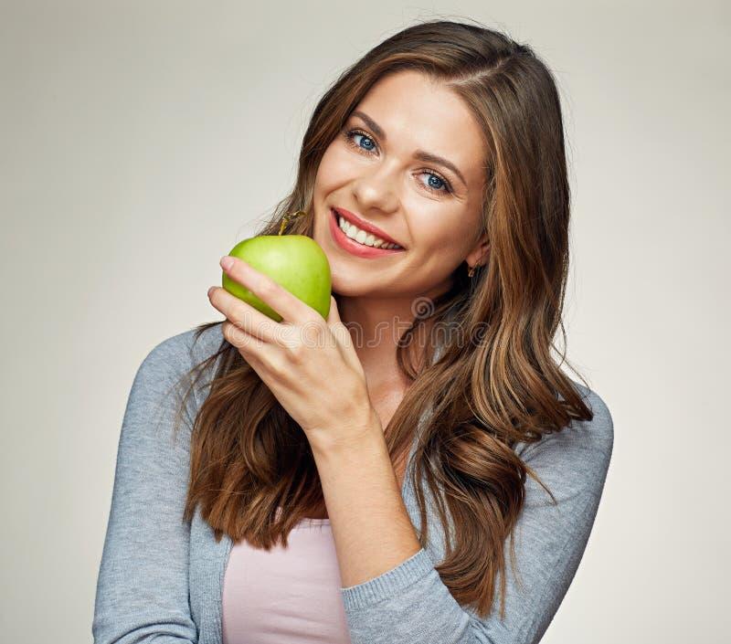De glimlachende vrouw bijt groene appel stock afbeelding