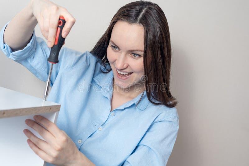 De glimlachende vrouw in blauw overhemd met schroevedraaier verdraait de schroef royalty-vrije stock foto