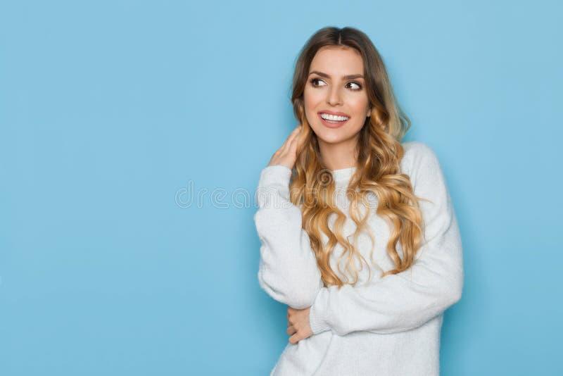 De glimlachende Vrouw in Blauwe Pastelkleursweater kijkt weg stock foto's