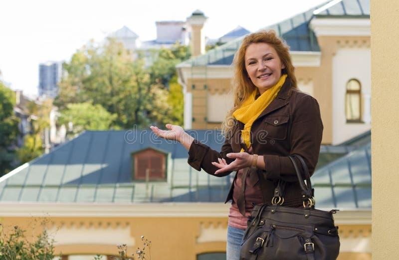 De glimlachende vrouw die de makelaar in werking stellen toont onroerende goederen stock foto's