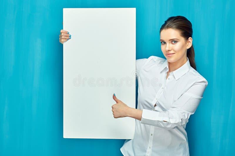 De glimlachende vrouw die grote witte tekenraad houden toont duim stock afbeeldingen