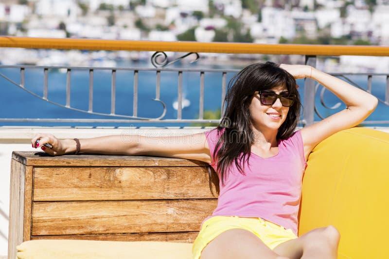 de glimlachende vrouw die van de de zomervakantie genieten die op a liggen sunbed in een overzeese bar royalty-vrije stock foto's