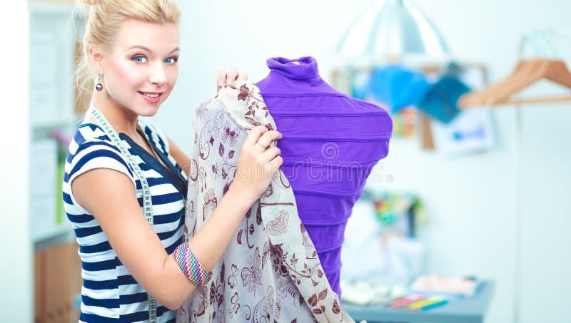 Download De Glimlachende Vrouw Die Van De Manierontwerper Zich Dichtbij Ledenpop In Bureau Bevinden Stock Foto - Afbeelding bestaande uit smiling, wijfje: 107704736