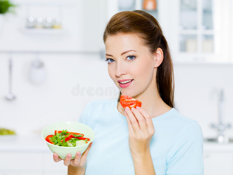 De glimlachende vrouw eet groente stock foto's