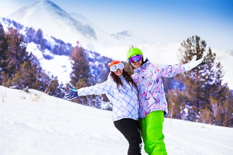 De glimlachende vrouw en de man in skimaskers omhelzen handen stock afbeelding