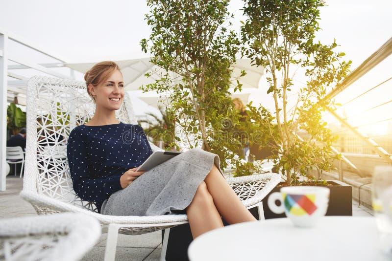 De glimlachende vrouw gebruikt digitale tablet, terwijl in bar ontspant stock afbeelding