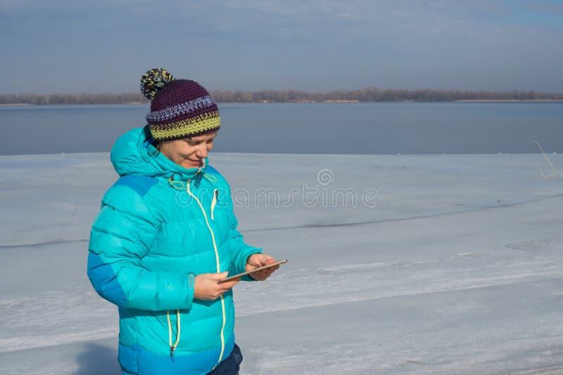 De glimlachende vrouw gebruikt een tabletpc voor mededeling stock afbeelding